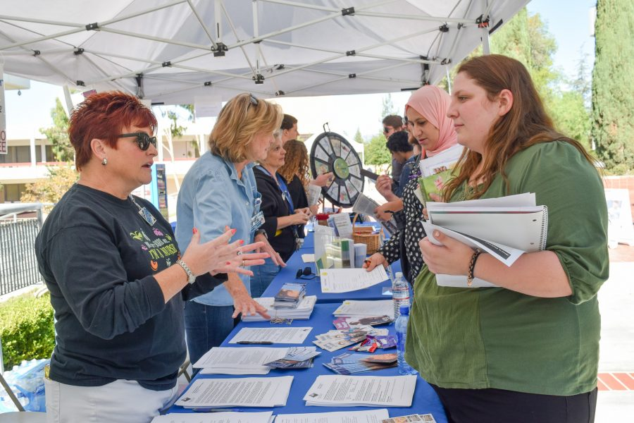 """Dena Steven, Moorpark College Nurse, speaks with Child Development major Gina Bois, 18, about the overall services available at the Student Health Center during the College's Health Fair on the Raider Walk, Oct. 4. """"If I had a nickel every time a student doesn't know we have a student health center I would be a rich woman,"""" said Allison Barton, Campus Health Educator. Photo credit: John Louie Menorca"""