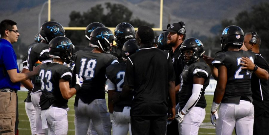 Moorpark College Football players huddle around coach Mike Stuart after a called timeout by Moorpark Photo credit: Conrad De Santiago