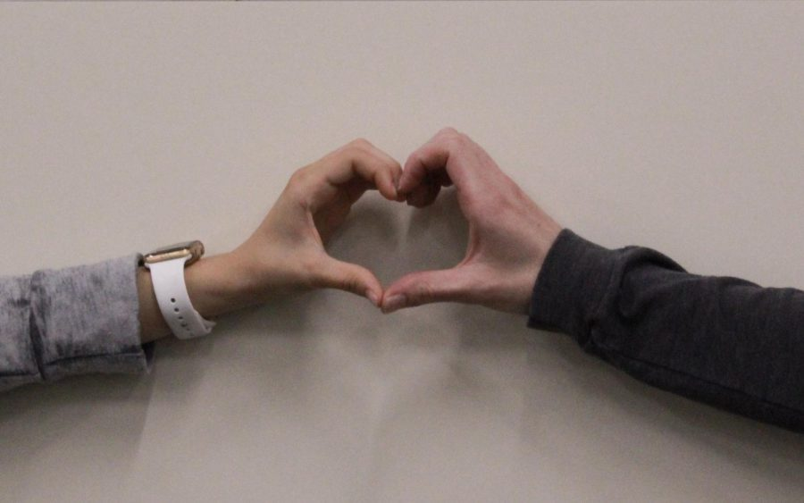 Two students form  heart with their hands to promote love. Photo credit: Shariliz Poveda
