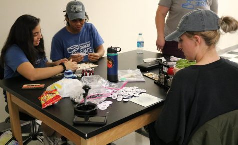 MakerSpace team members work together to make buttons showcasing the design of another student in the program. Photo credit: Michelle De Leon