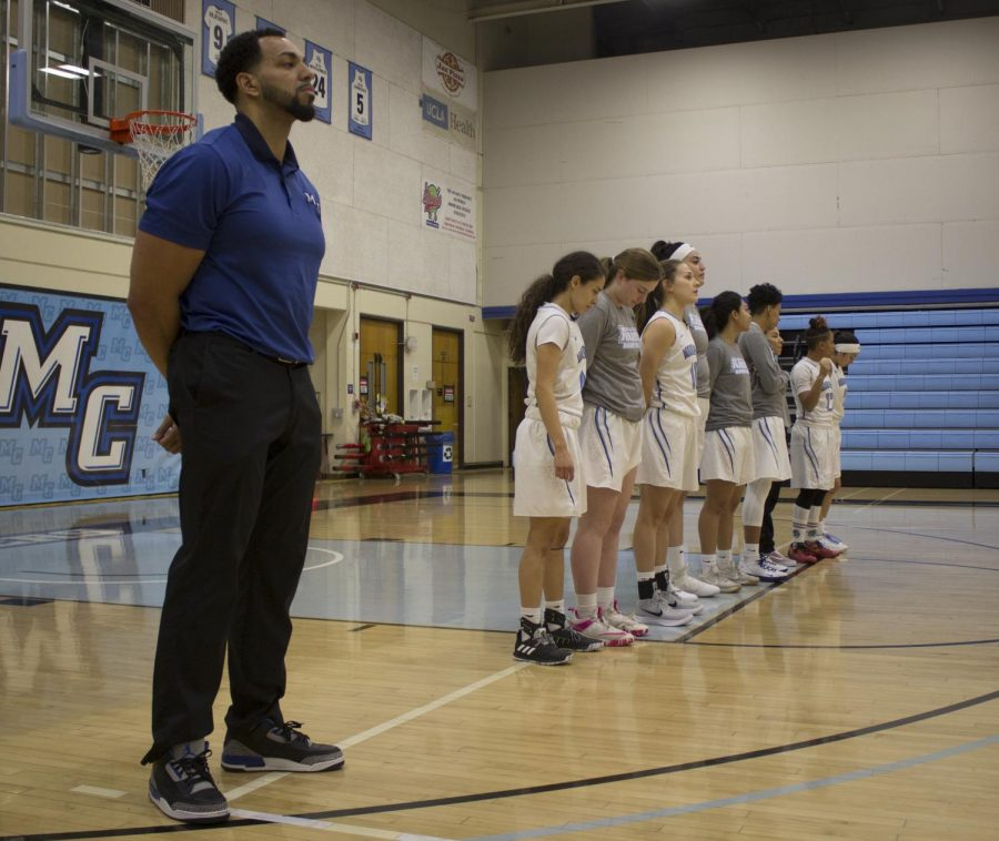Head Coach Kenny Plummer, left, stands for the national anthem alongside the women's basketball team before their game against Ventura College in the Moorpark College gym, on Feb. 6, 2019. Photo credit: Evan Reinhardt