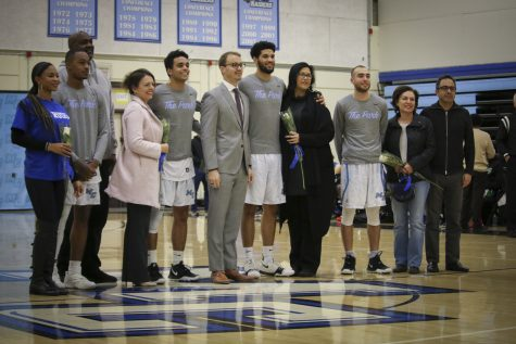 Graduating sophomores stand with parents and Head Coach Gerred Link, center, in honor of their last home basketball game of the season on Tuesday, Feb. 19, in the Moorpark College gym. In celebration, each sophomore started in the game against Oxnard College. Photo credit: Evan Reinhardt