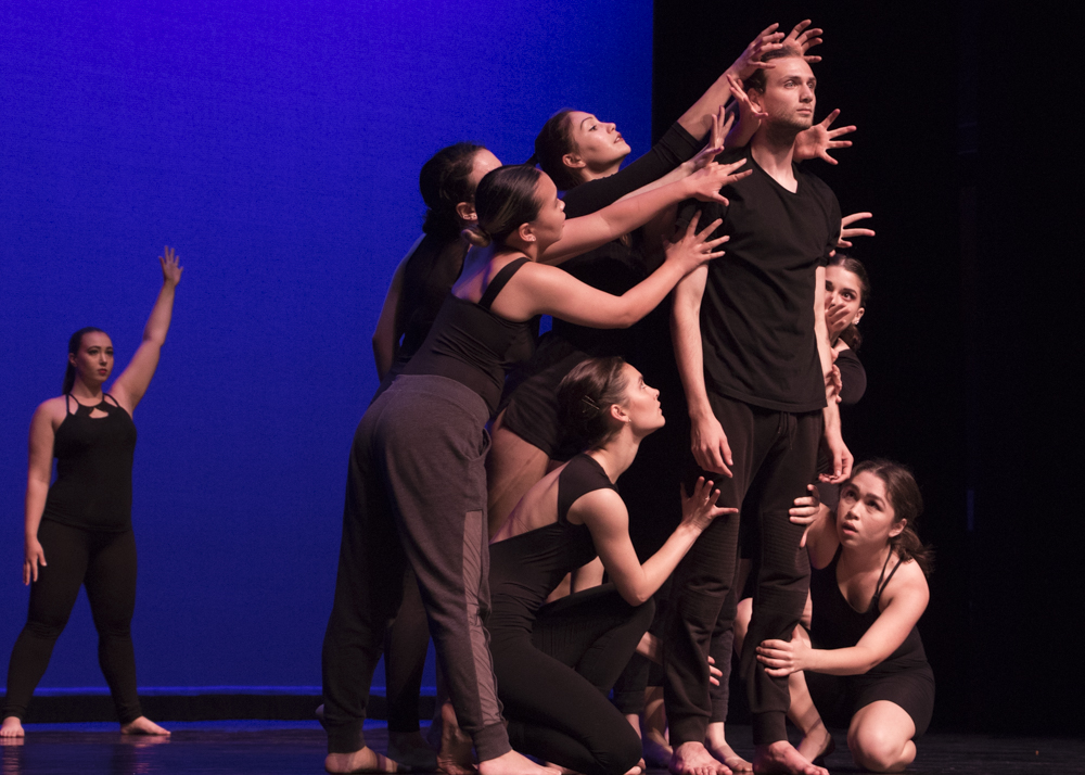 Students of the performing dance ensemble class surround fellow student, Kevin Holland, 20, during their dress rehearsal performance on Wednesday, May 15, in the Performing Arts Building. Holland has become a member of the National Honor Society of Dance Arts, and hopes to help more people learn to dance. Photo credit: Evan Reinhardt