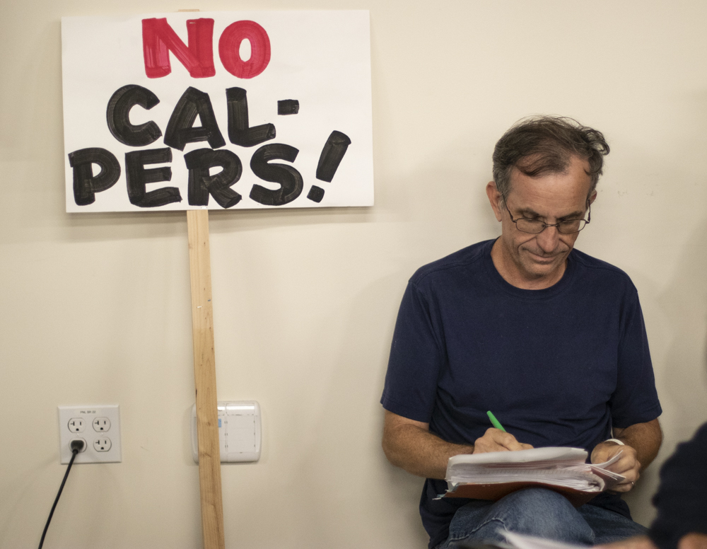 Joe Selzler, chemistry professor at Ventura College, grades papers as he protests the Trustees' proposal during the open session meeting on Tuesday, Sept. 10, in Camarillo, Calif. According to Selzler, full-time professors have gone three years without a raise, and a fourth would be,