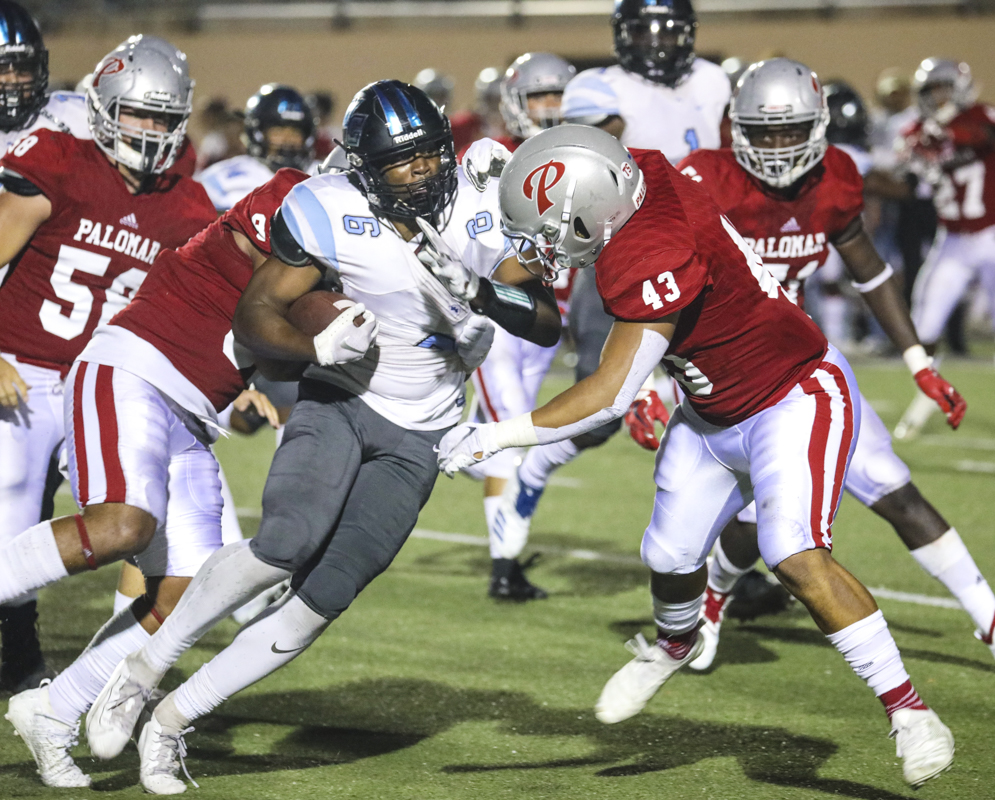 Sophomore running back Edyon Batta, 6, smashes through the defensive line during the Sept. 7 game against Palomar College, in San Marcos, Calif. Photo credit: Ryan Bough