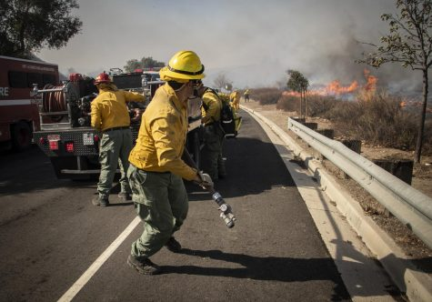 Firefighters unspool hose as the flames of the Easy Fire approach East Olsen Road in Simi Valley, Calif. on Wednesday, Oct. 30. Photo credit: Evan Reinhardt