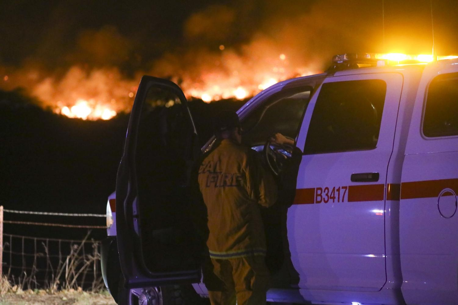 A CAL FIRE firefighter speaks with a colleague as they watch the Wendy Fire being extinguished on Oct. 10 in Newbury Park. Photo credit: Ryan Bough