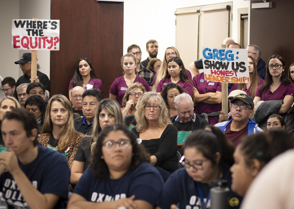 The crowd holds up various protest signs during the Board of Trustee meeting on Tuesday, Nov. 12 in Camarillo, Calif. Most of the crowd consisted of VCCCD staff and faculty. Photo credit: Evan Reinhardt