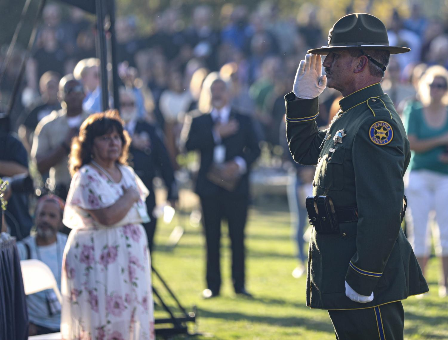 Sgt. Pat Ruby salutes during the singing of the national anthem at the dedication for the new Healing Garden in Thousand Oaks on Nov. 7. Hundreds of community members gathered to pay respects to the lost souls. Photo credit: Ryan Bough