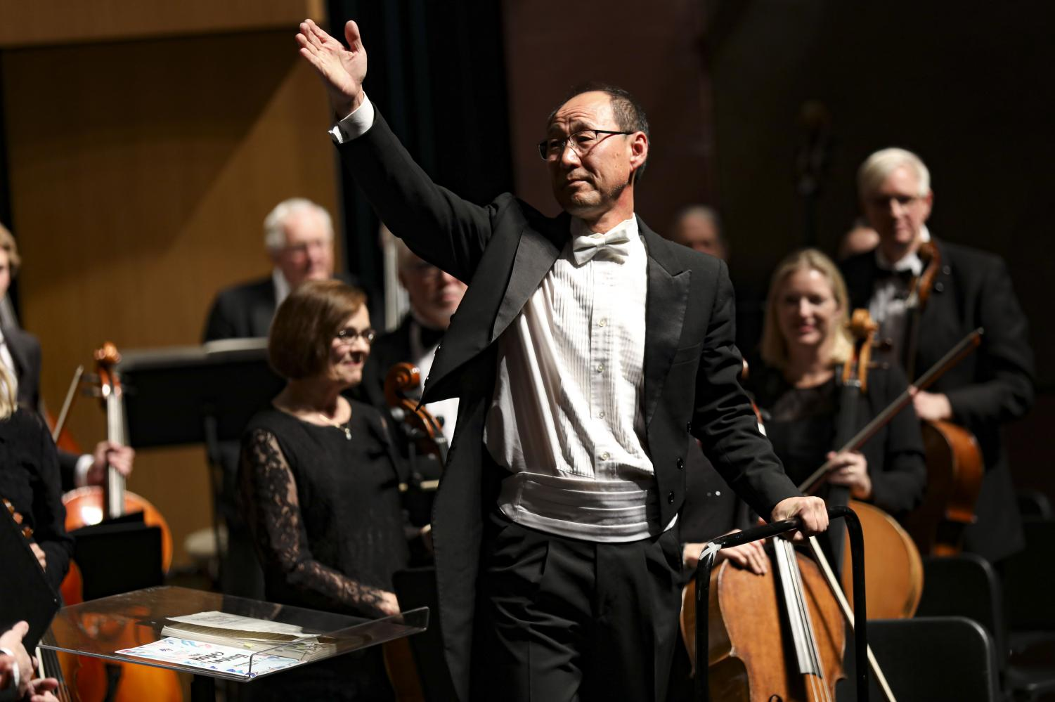 Conductor James J. Song points out the musicians that played especially well as the audience erupts into applause at the end of the