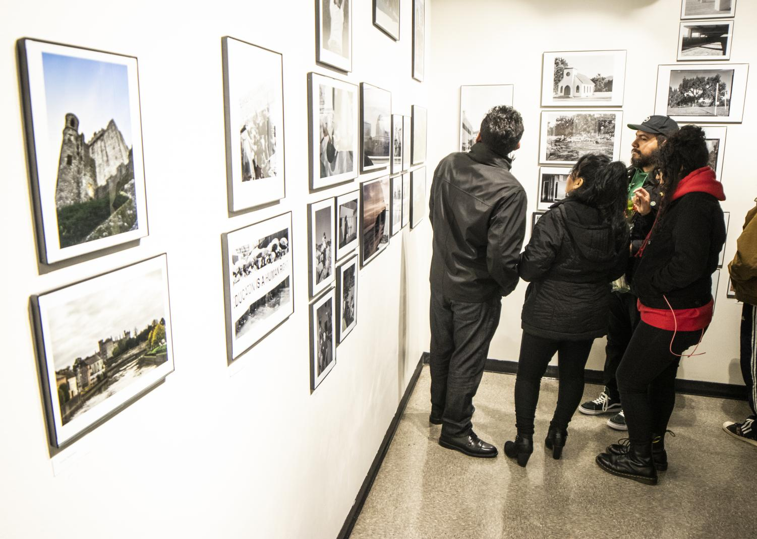 The Perez family views the works on display during the Work in Progress photo gallery on Wednesday, Nov. 21 in the Humanities building. Daniel Perez had work on display through participation in the Intermediate Photography class. Photo credit: Evan Reinhardt