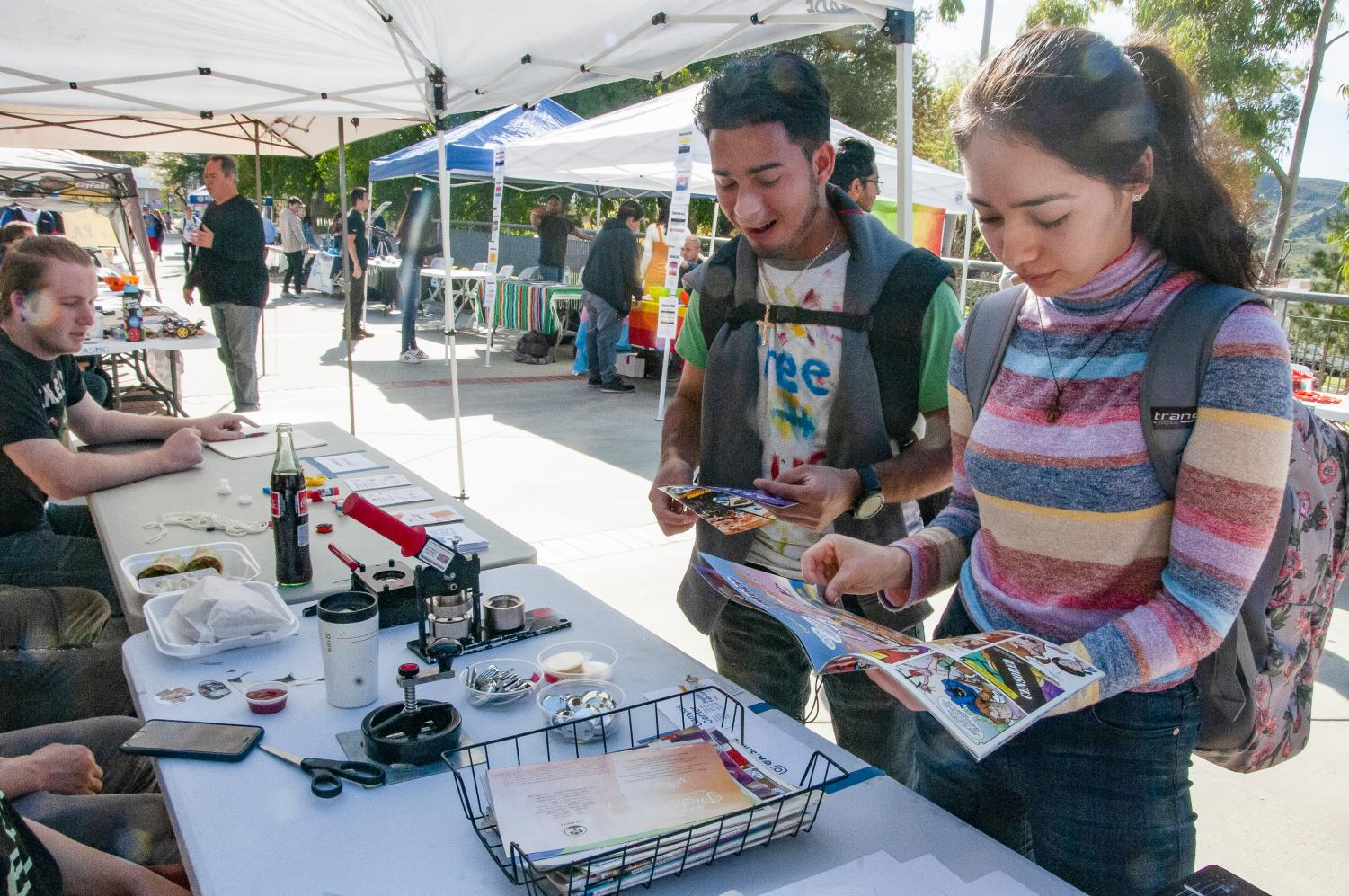 Carlos Hernandez, left, and Carmen Fregoso talk with representatives of the Moorpark College MakerSpace booth at Club Rush on Tuesday Jan. 28. Hernandez and Fregoso were making complimentary custom pins with materials set out by the club. Photo credit: Morgan Ellis