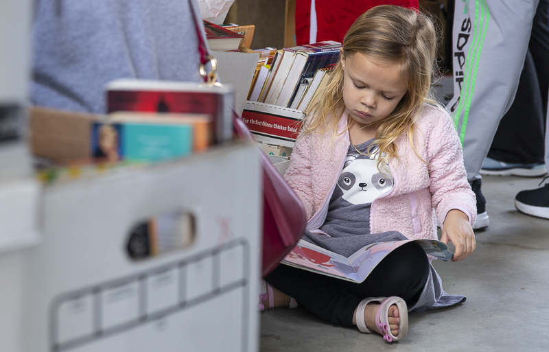Quinn Portillo, four and a half-year-old, flips through one of the many books available during the book sale at the Moorpark Public Library on Saturday, Feb. 22.