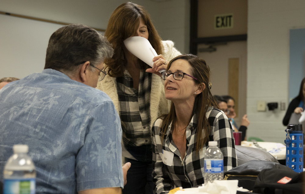 Professor Linda Kushner whispers into the ear of Learning Disabilities Instructor Sile Bassi during the Mental Health First Aid Certification session on Thursday, Feb. 6, in LMC 125. The activity was meant to simulate what a conversation is like with schizophrenia. Photo credit: Evan Reinhardt