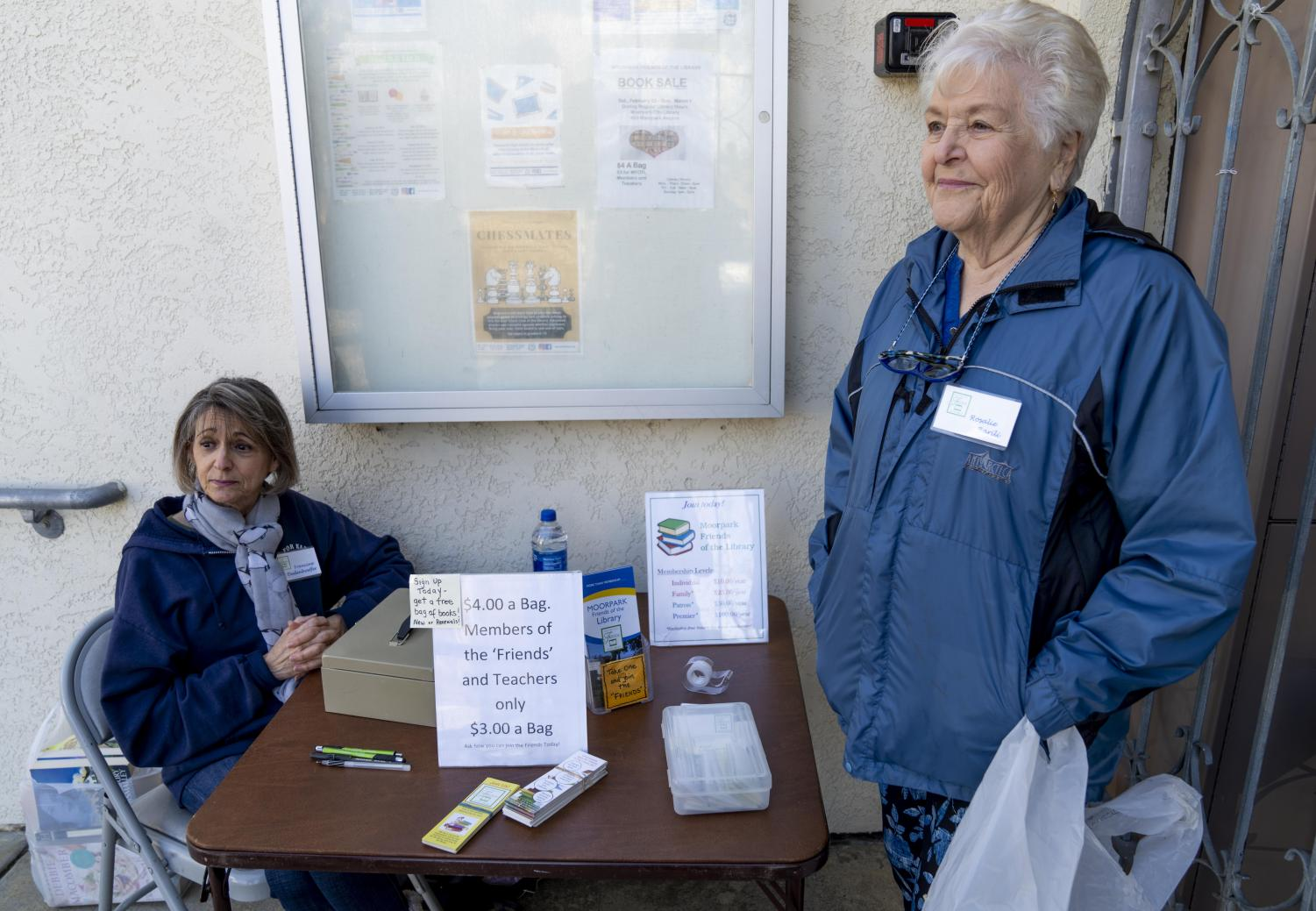 Francine Dudenhoeffer, left, alongside Rosalie Barili, talk about their history in the library during the book sale hosted by the Friends of the Library on Saturday, Feb. 22.
