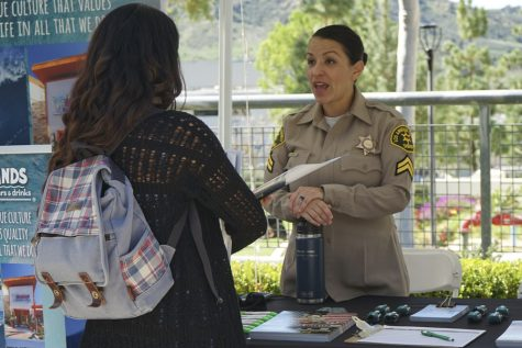 Deputy Weber, 37, from Santa Clarita, informs Moorpark College Biology student Marisol Gonzalez about what jobs the LAPD has to offer at the career expo on March 3. Photo credit: Gavin Woods