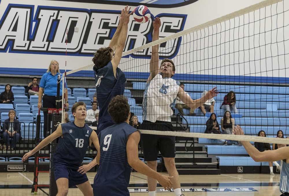 Sophomore setter Lucas Ogg jumps up to joust with the Warriors' middle blocker during Moorpark's home game on Wednesday, March 4.