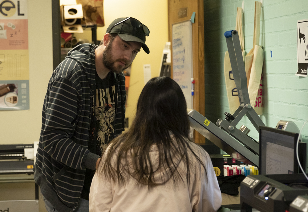 Mike Dupree, former Moorpark College student, receives help from MakerSpace staff to print a self-designed T-shirt on Monday, March 2.