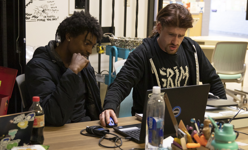 Darien Wade watches as Keir Kloss assists him in scanning a drawing into a digital format in MakerSpace on Monday, March 2. Wade plans on using the design for a T-shirt.