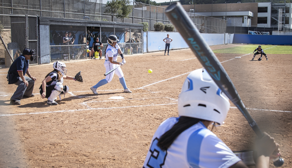 Freshman Ylse Prieto takes a swing at bat for the raiders during their home game on Saturday, Feb. 29. Freshman Bethany Yzaguirre waits on deck studying the pitch.
