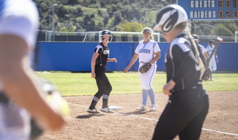 A Renegade base runner watches from third base next to Raider third baseman Alexis DeYoung after the Renegades brought home a batter during moorpark's home game on Saturday, Feb. 29. Photo credit: Evan Reinhardt
