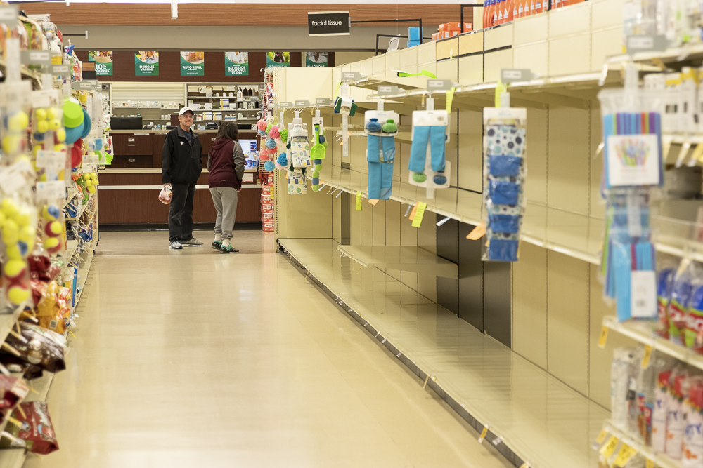 Shelves formerly carrying facial tissue lay empty after customers clear the store's stock on Thursday, March