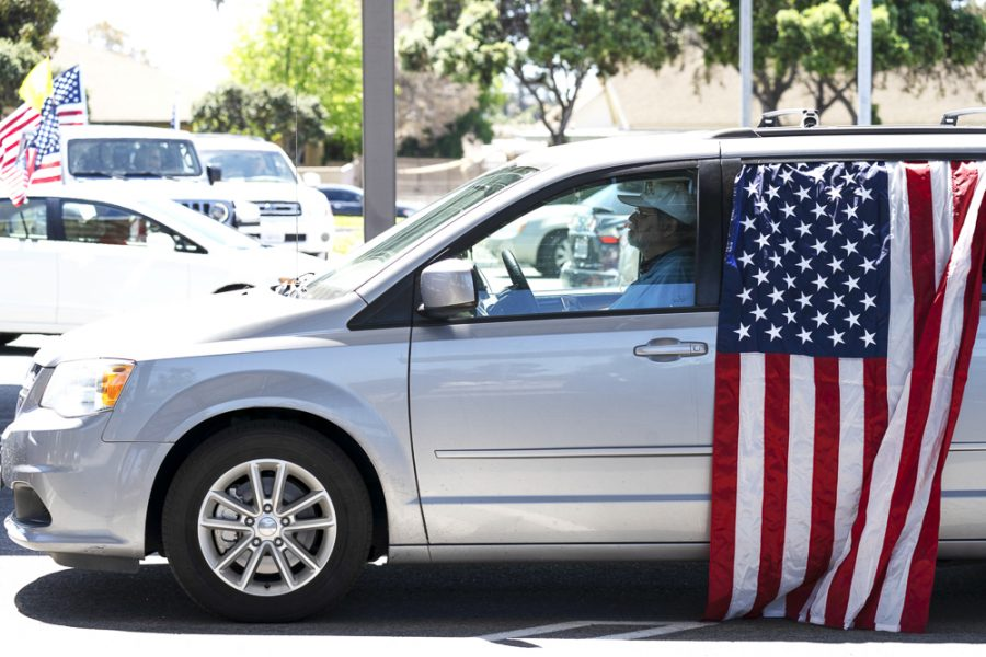 Protesters begin the demonstration in the Ventura County Government Center parking lot in their cars, holding signs and flags, on Friday, April 24, in Ventura, Calif. The protesters were honking their horns, campaigning to open the government in Ventura County. Photo credit: Tara Brown
