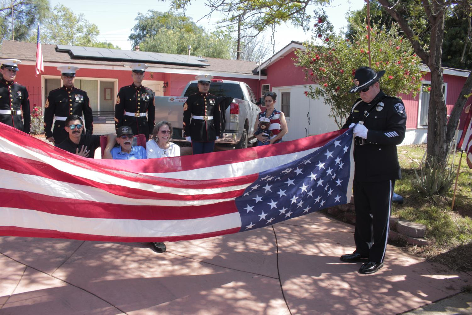 Andreas Pongo, Carlos Pongo and Katheryne Steffen watch as Simi Valley Police Dept. Honor Guard OFC Joe Pesce performs the flag-folding ceremony at the Pongo home in Simi Valley as members of the U.S. Marine Corps stand watch on April 26, 2020. The flag was presented to Carlos Pongo, father of Diego Pongo who was killed in action in Iraq.