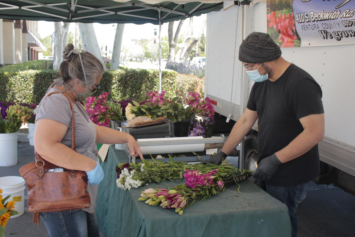 Doris Cox from Simi Valley purchases flowers from Mario Lopez of Santa Paula at the Simi Valley Farmers Market on April 24, 2020.