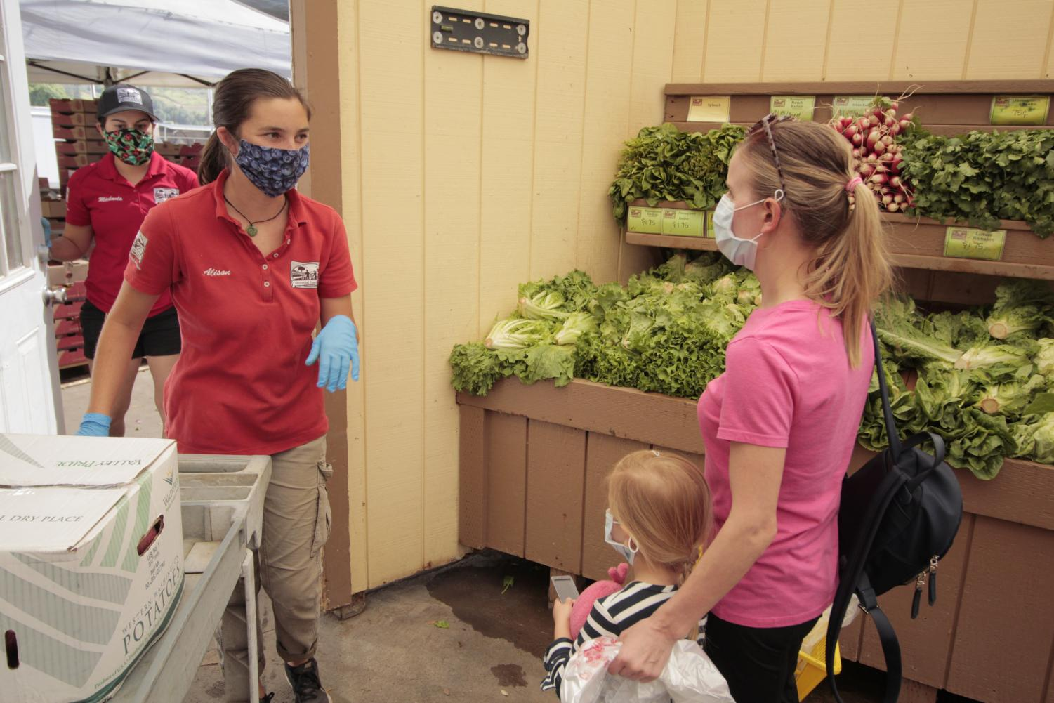 Underwood Farms employee Alison Hall helps Lena Pierson and Ella Pierson, 3, from Simi Valley as they shop for produce in Moorpark on April 28, 2020.