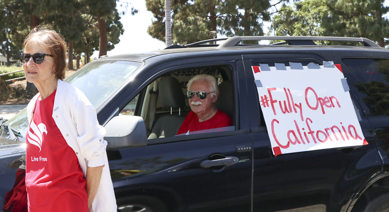 "Karen, on left, and George Rakowski prepare for the ""Reopen California"" protest held at the Ventura County Government Center on Friday, May 1."