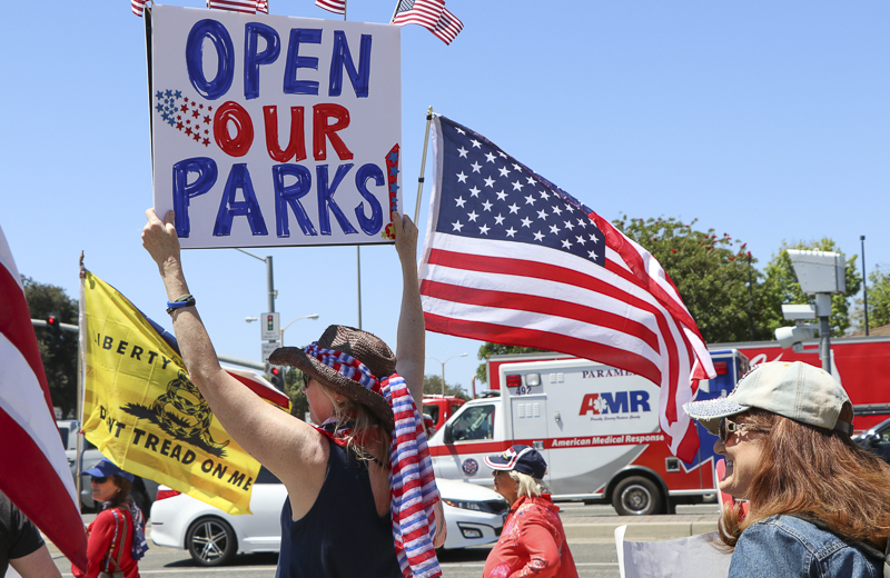 Ventura County community members gather to show their desire for the reopening of California at a protest on Friday, May 1 at the Ventura County Government Center. Many carried patriotic signs and flags to support their cause.