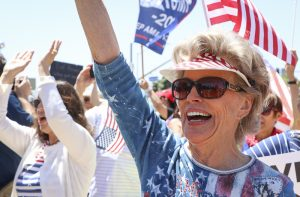Dea Coletti shows her support for the reopening of California at a protest held at the Ventura County Government Center on Friday, May 1, in Ventura, Calif. Community members gathered in patriotic clothing with signs and flags to help convey their message. Photo credit: Morgan Ellis