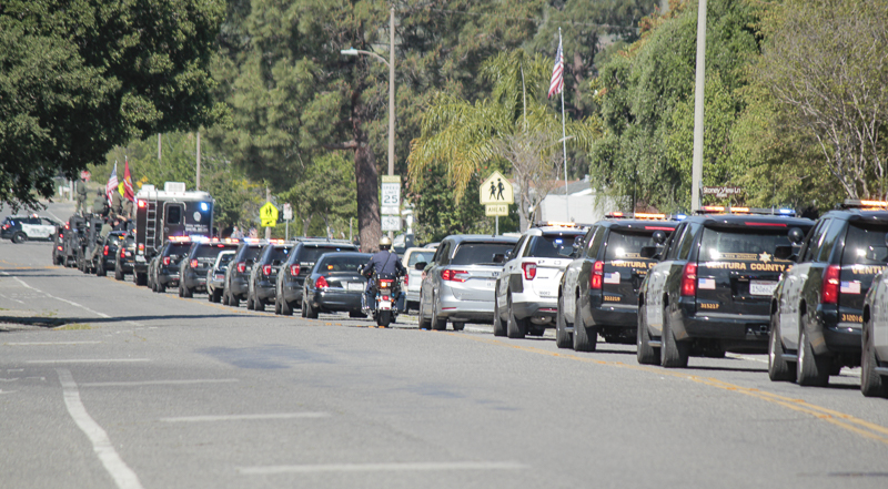 Police cars and civilians line up for a parade on Katherine Ave. in Simi Valley on April 26, 2020 which honored Marine Gunnery Sergeant Diego Pongo who was killed last month in Irag. Due to COVID-19, the family is not able to hold an official burial.