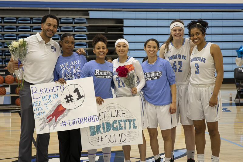 From left to right, Head Coach Kenny Plummer poses for a photo with the sophomore players Bridgette Smith, Bree Calhoun, Jazzy Carrasco, Isabel Ayala, Caleigh McClenahan and Britt Van Buren prior to their home game against Oxnard College on Friday, Feb. 21.