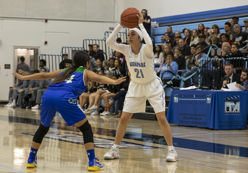Jazzy Carrasco looks for her team past a defender in Moorpark's home game against Oxnard College on Friday, Feb. 21, 2019.
