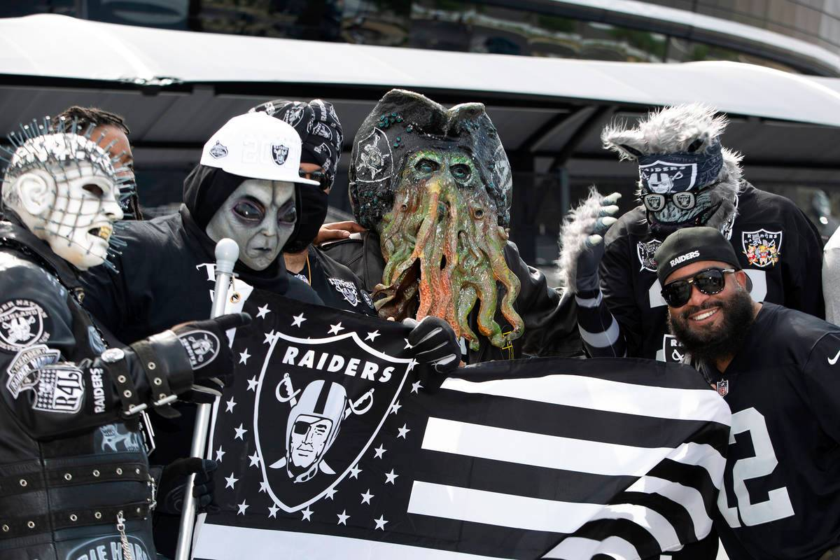 Patrick Beckett of New Jersey poses for a photo with Raiders fans in costumes as fans congregate before the first home game of the season outside the newly built Allegiant Stadium on Monday, Sept. 21, 2020, in Las Vegas. (Ellen Schmidt/Las Vegas Review-Journal)