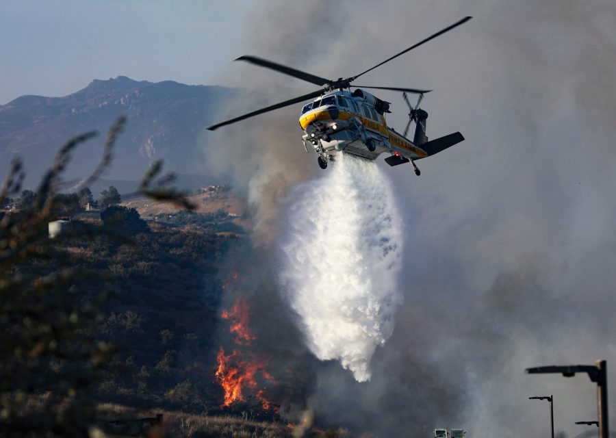 An emergency helicopter drops water and fire retardant on to the Easy fire on Wednesday, Oct. 30, 2019, in Simi Valley, Calif. Photo credit: Ryan Bough