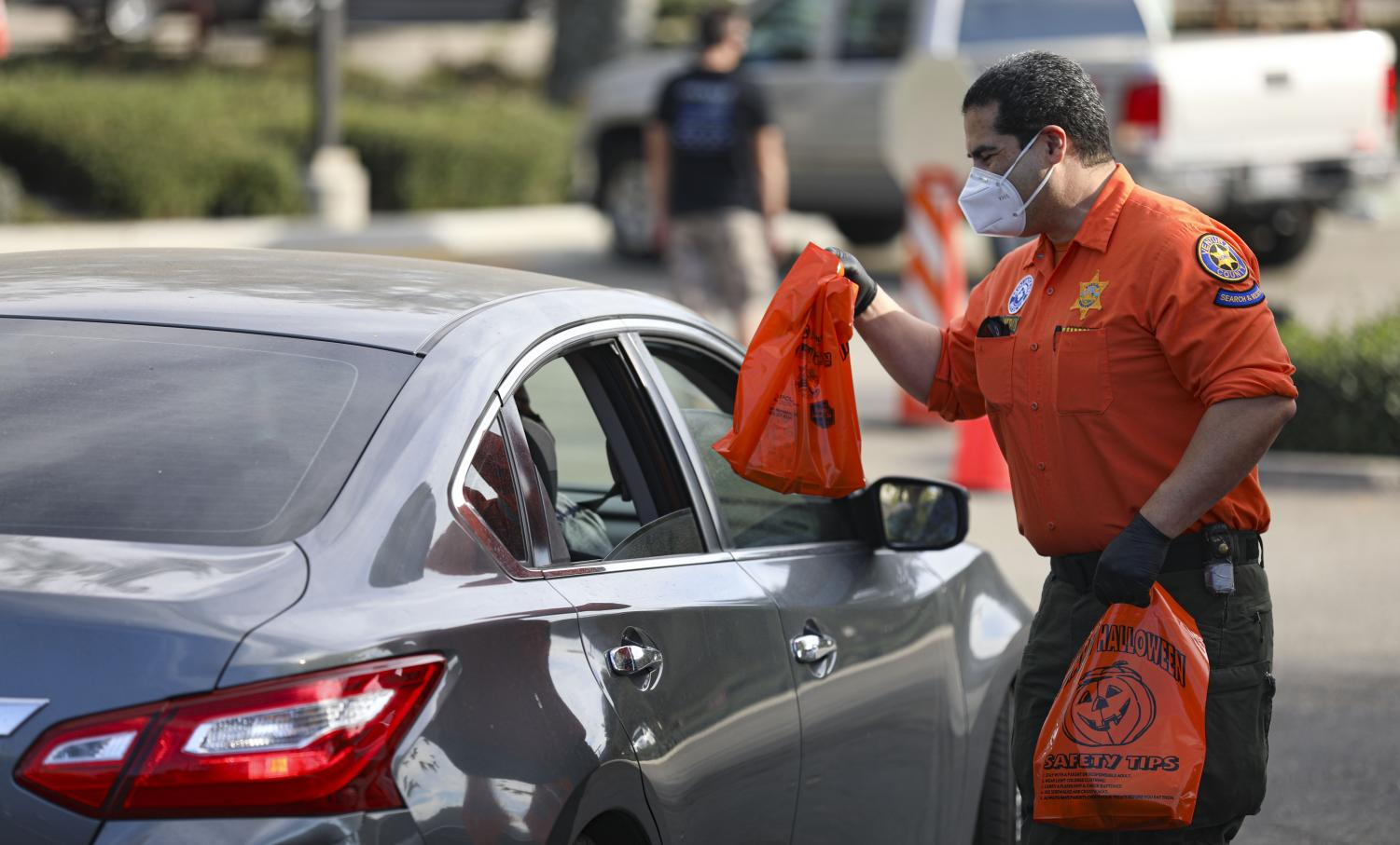 Bo Medina hands over bags of candy to trick or treaters during the