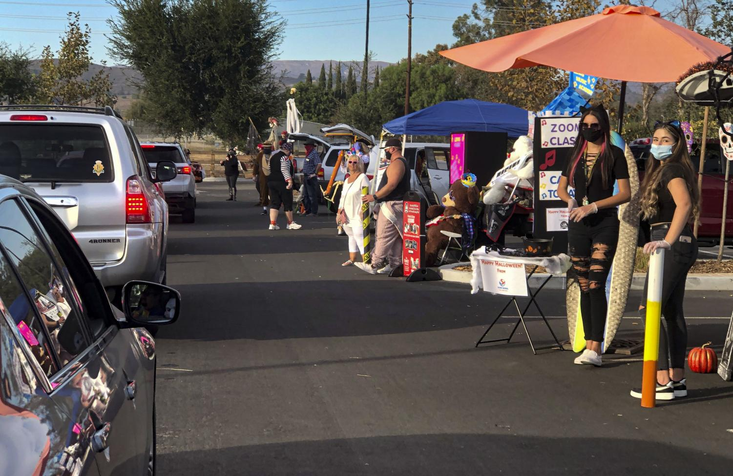 Local businesses pass out candy to cars in line at the Spooky Avenue Halloween drive-thru in Moorpark, CA. on Saturday, Oct. 31.