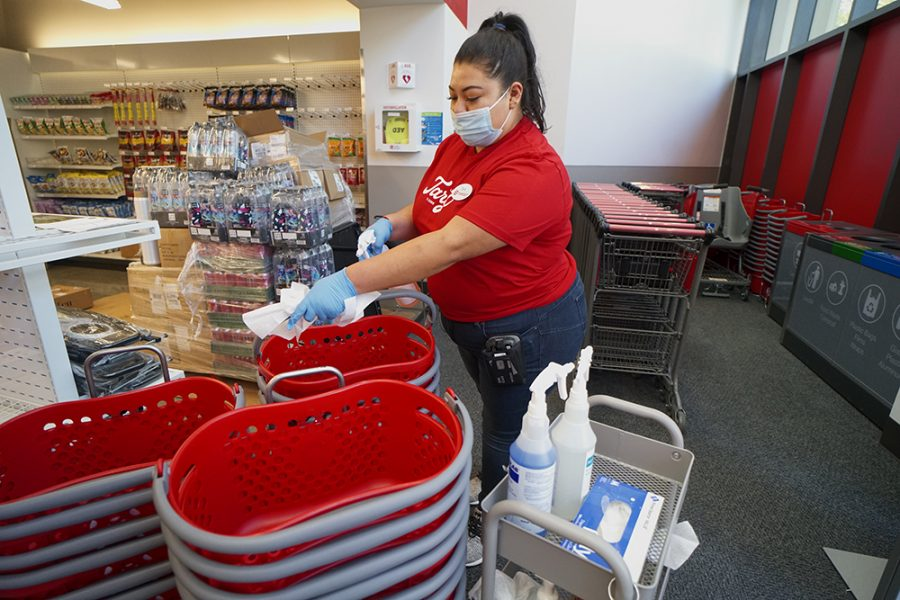A Target team member sanitizes shopping carts and baskets between uses as past of the increased cleaning and sanitizing routines throughout Target stores on Monday, Oct 19 in San Diego. Image courtesy of (Sandy Huffaker/AP Images for Target)