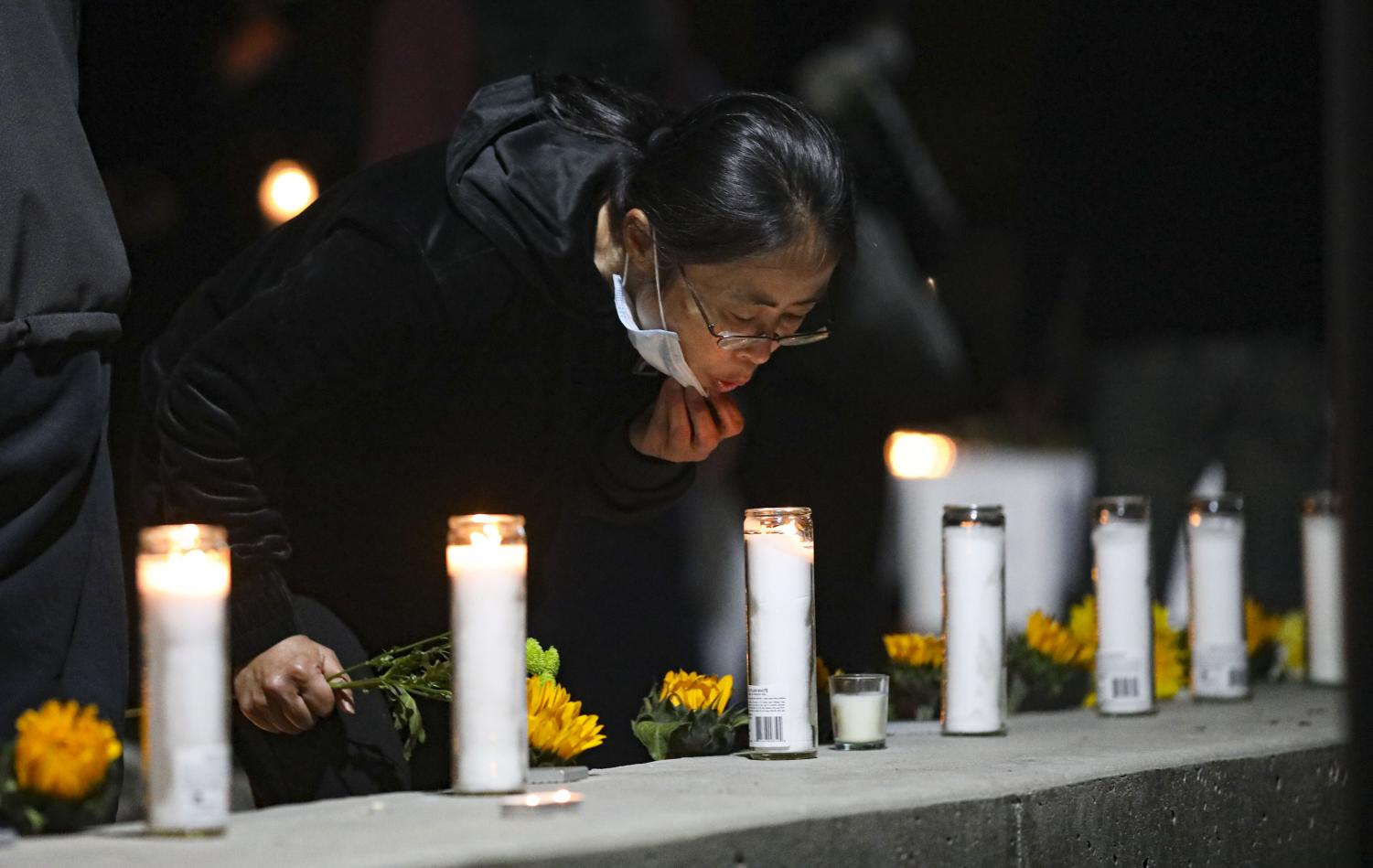Pam Wang blows out the candles places to remember the eight lives lost