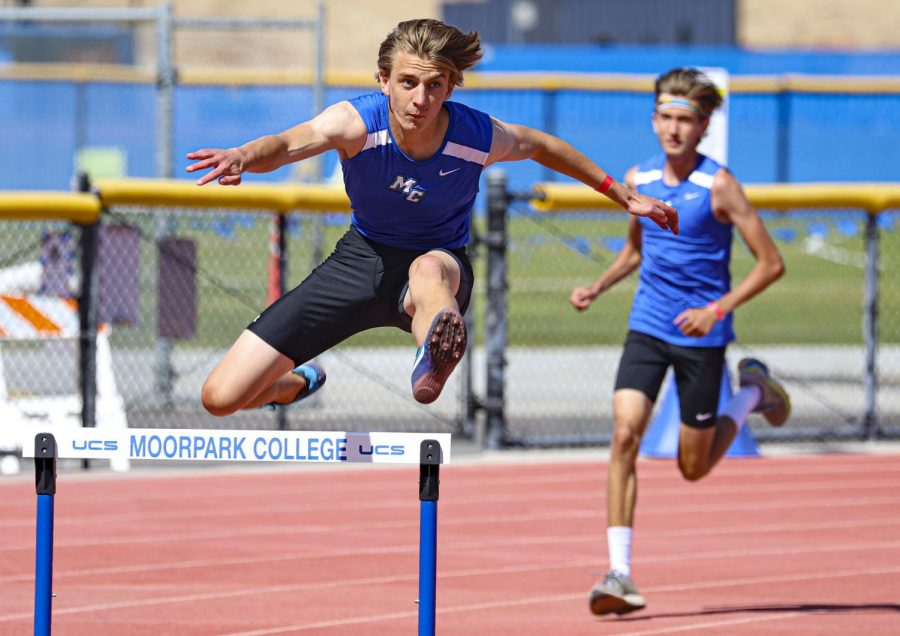 Jack Franklin jumps over a hurdle as Basilio Vives trails behind during the men's 110 meter hurdles race at the first WSC meet of the season on Friday, April 16, 2021 in Moorpark, CA. Photo credit: Ryan Bough