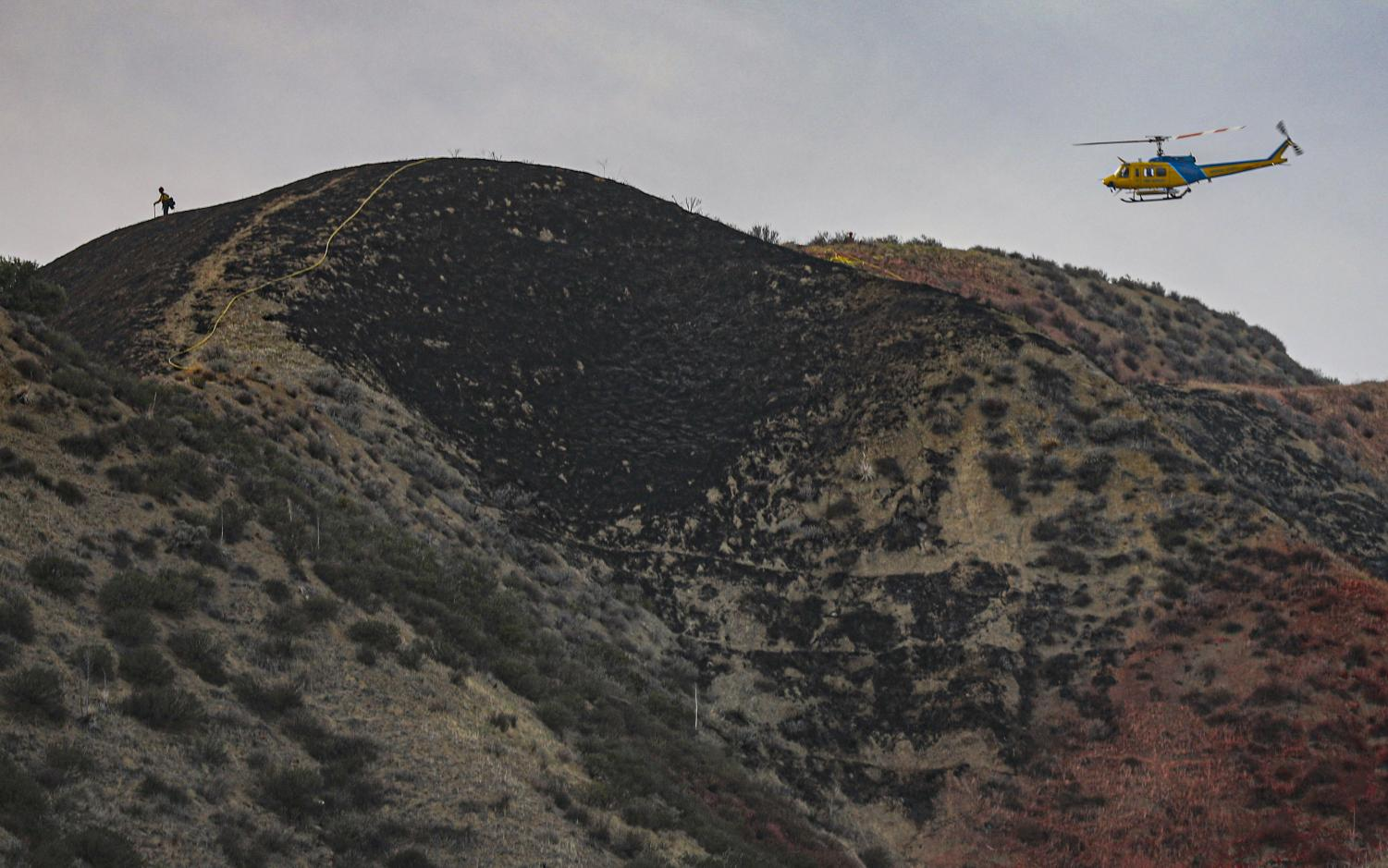 Ventura County firefighters put out hotspots on top of the charred hill from the Westwood fire in Simi Valley, CA. on Sunday, April 4, 2021. The Westwood fire grew to 25 acres before forward progress was stopped.