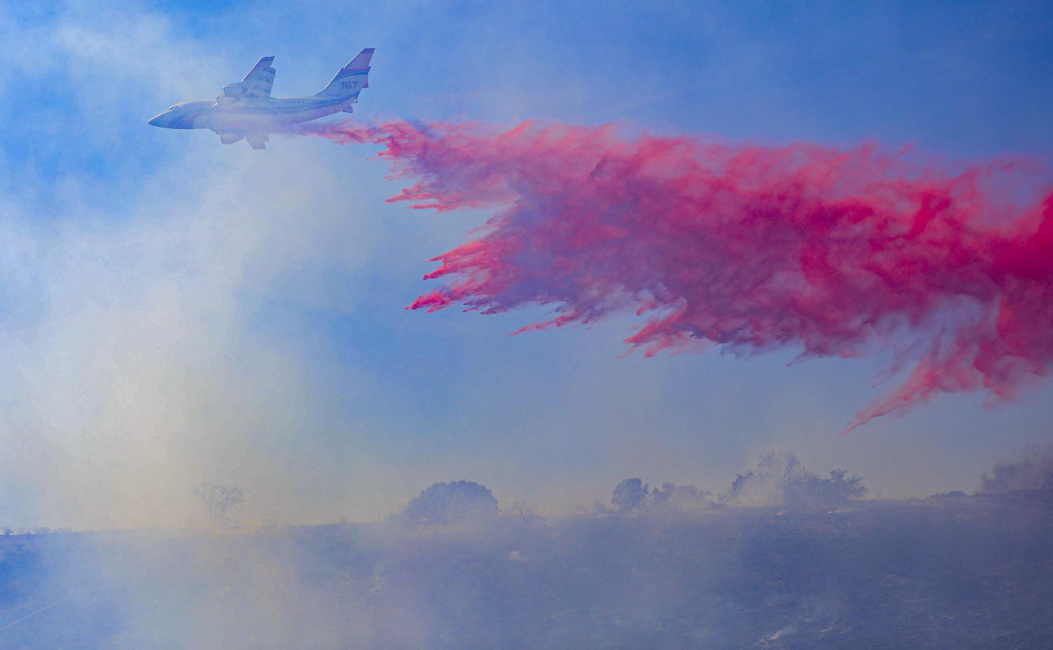 A Cal Fire plane drops fire retardant ahead of the Country Fire to halt its forward progress on Thursday, April 29, 2021.