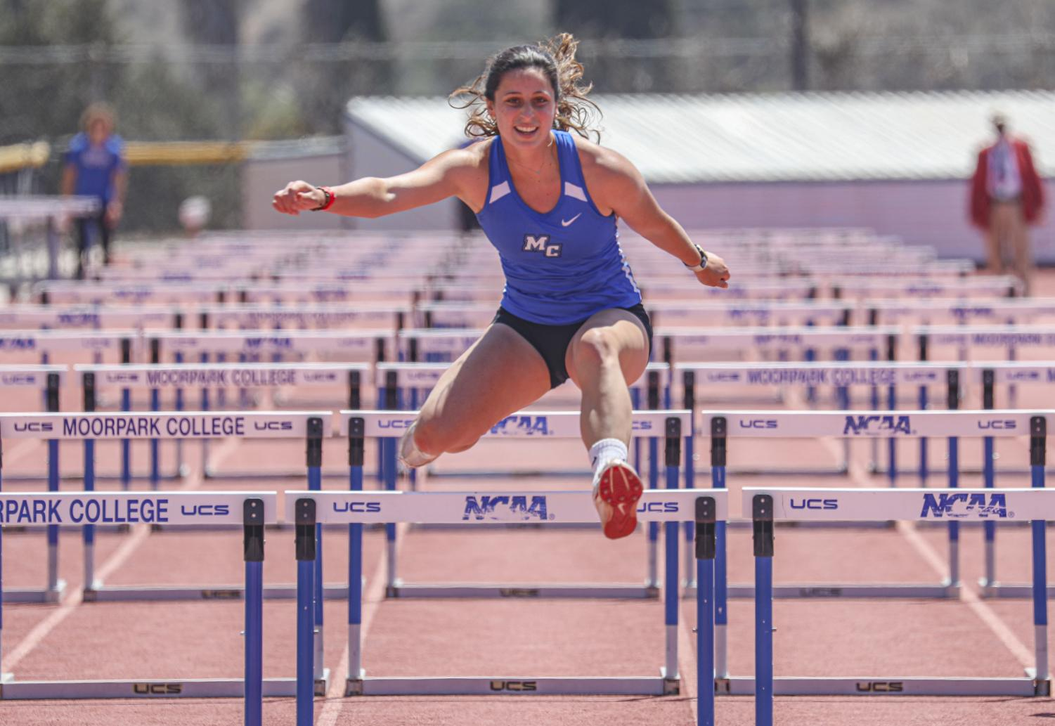 Annie Doherty jumps over the last hurdle during the 100 meter hurdles race