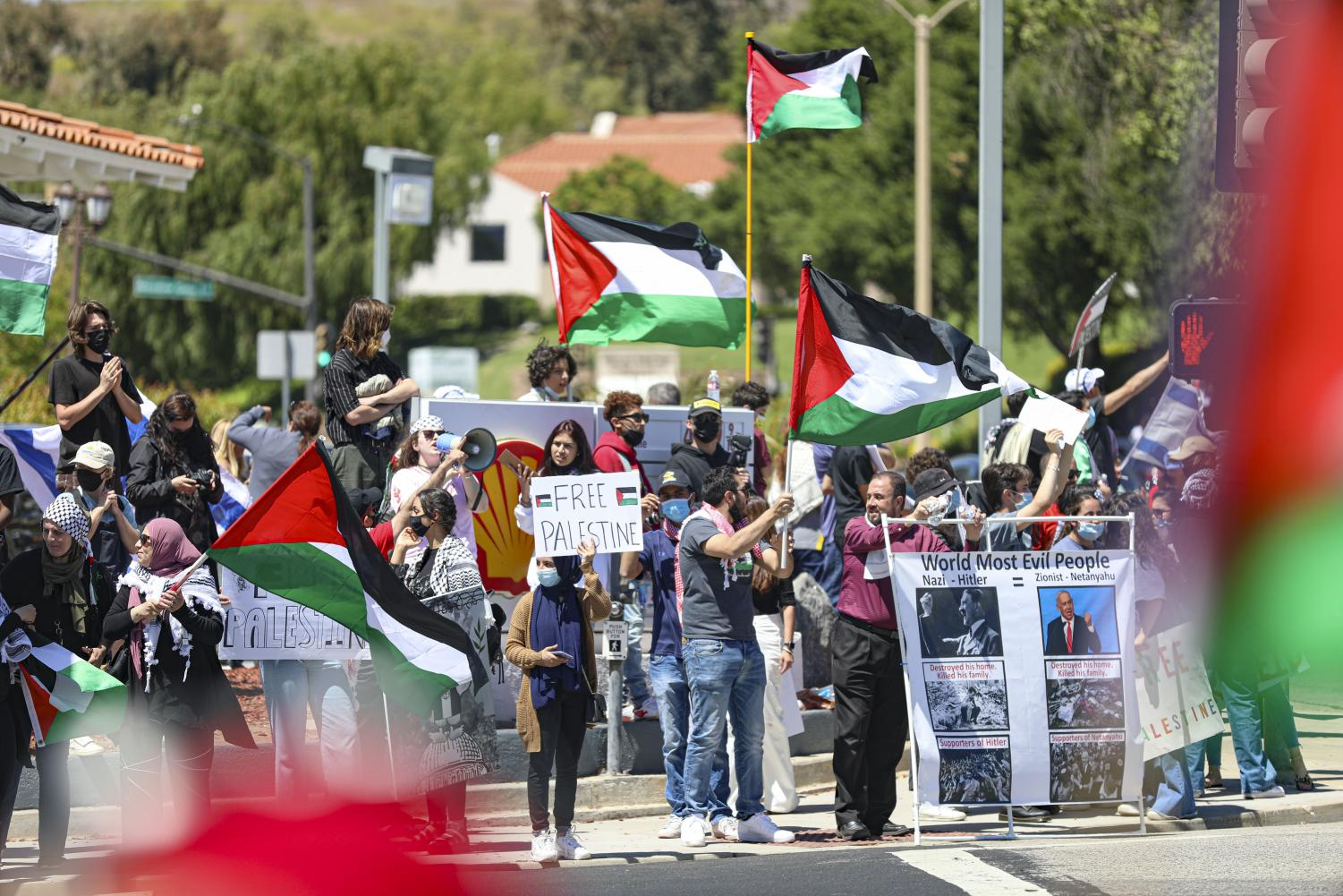 Pro-Palestine protesters hold signs and flags in support of Palestine during a protest in Thousand Oaks, CA. on Sunday, May 23, 2021.