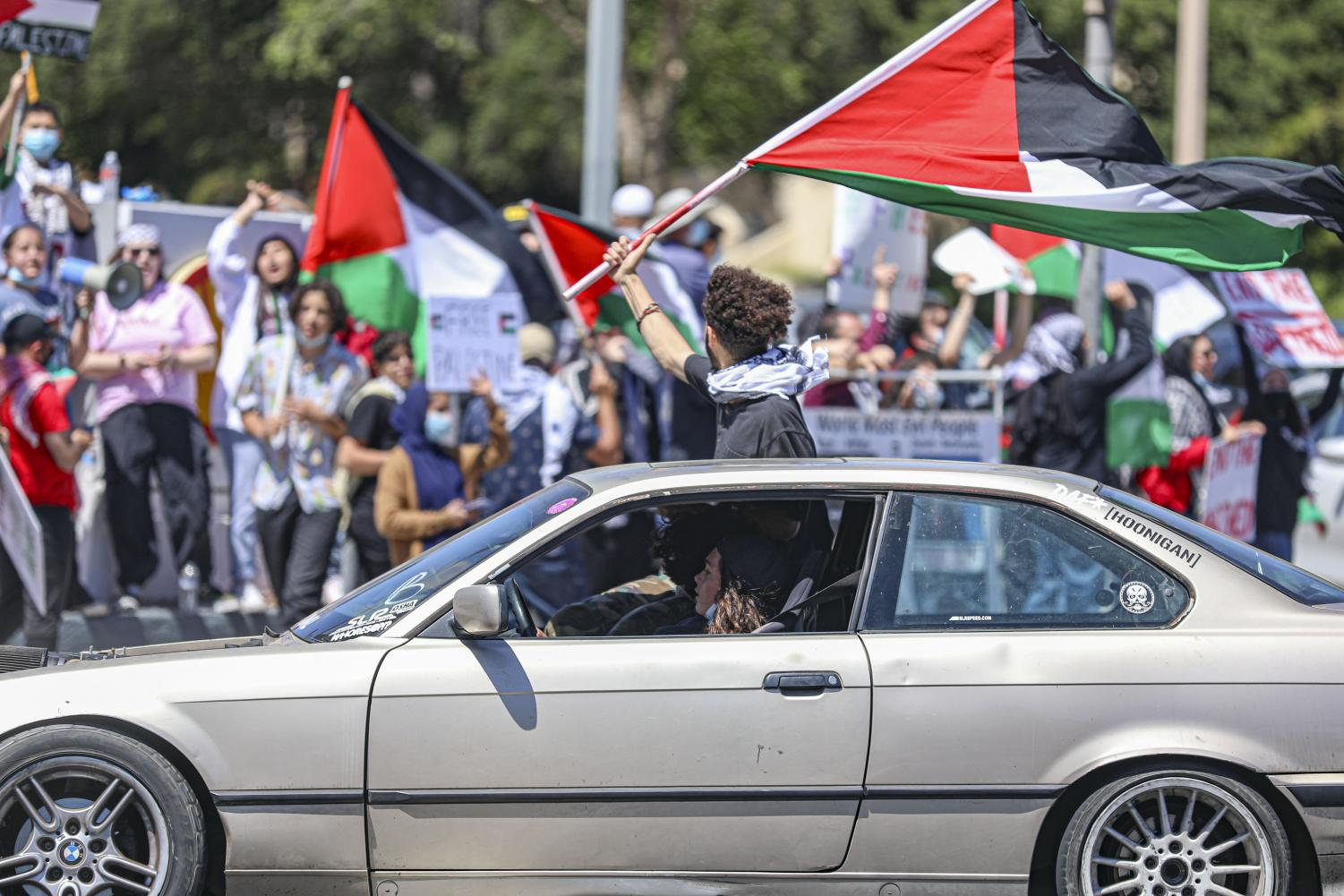 A protester hangs out of a car window waving a Palestine flag during the pro-Palestine protest in Thousand Oaks, CA. on Sunday, May 23, 2021.